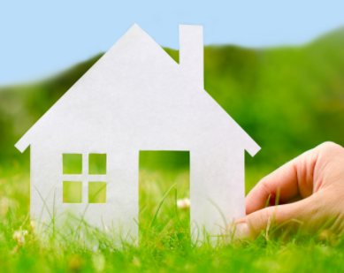 Image of hand holding a paper cutout of a house